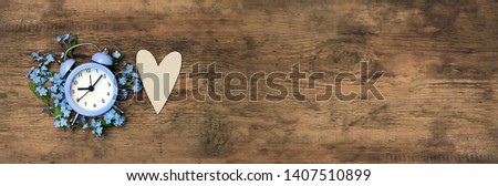 heart and clock alarm with flowers on old wooden background. concept make time for nature, environment. hello spring season. spring season. copy space. top view, banner