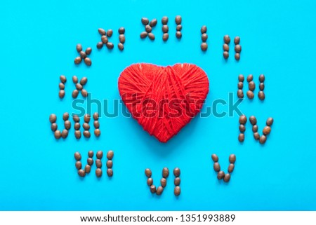 Heart and clock made of cocoa beans on the blue background.