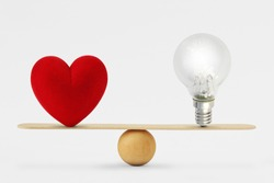 Heart and light bulb on scale - Concept of balance between heart and brain