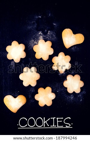 Heart and star shape cookies on the black wooden background from above