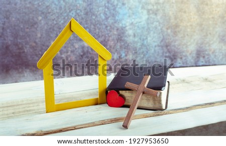 Heart and Wooden cross leaning on a bible, next to small yellow house wooden on white background. copy space Stock photo ©