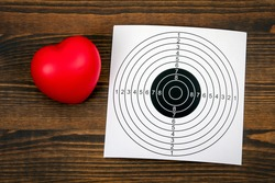 Heart attack, health problems or falling in love concept. Red rubber heart and paper target on a wooden background.