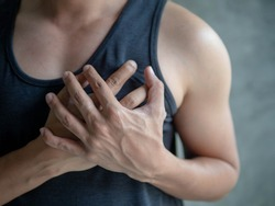 Heart attack symptom-Healthcare and medical concept.pressing on chest with painful expression.