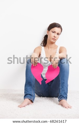 Heart-broken female sitting on floor sadly, holding a torn paper heart in hands.? - stock photo