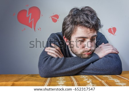 Heart broken man sitting at the desk with his arms crossed, little torn hearts floating above him #652317547