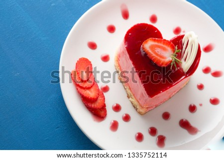 Heart Cake picture . Lovely delicious heart cake. A red colored cheesecake on a plate and a wooden table