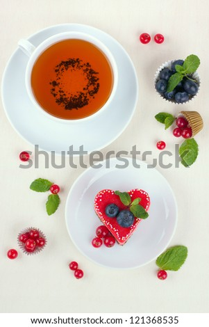 Heart cake with cup of tea and berries