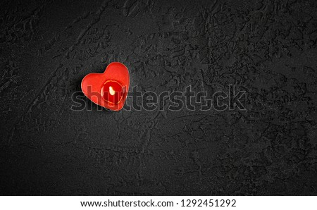 heart candle on black background. Love heart candle over dark background. simple style design for Valentine's day greetings. minimalism concept. valentines day concept or candle of memory, sorrow.