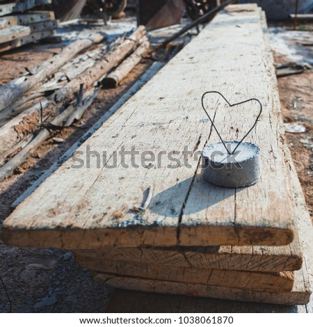 Heart created from steel wire on the concrete lump. Love symbol and sign on the wood. Abstract of love sign and symbol. #1038061870