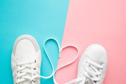 Heart created from white shoelaces between male and female sport shoes. Love concept. Top view. Empty place for lovely, cute text, quote or sayings on pastel blue and pink paper background. Closeup.