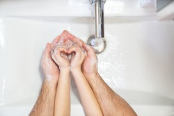 heart. dad teaches daughter thorough washing of hands soap foam and water