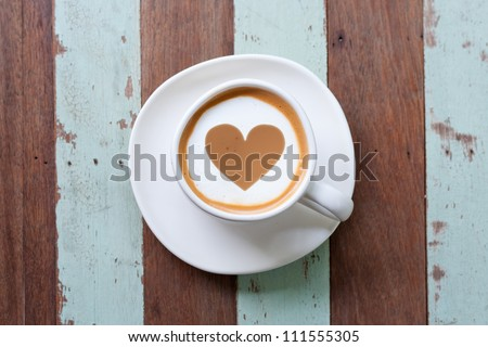 heart drawing on latte art coffee , wood color background
