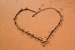 Heart drawn heart symbol on sand, seacoast. Golden sand beach close up, summer holidays concept. Tourist travel banner design template, copy space. Love symbol, heart shape.