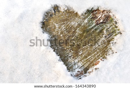 heart drawn in the snow on wood