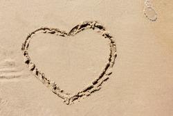 Heart drawn On Ocean Beach Sand. Heart shape drawn on the sandy beach. true love concept.