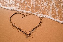 Heart drawn on sand, seacoast. Golden sand beach close up, summer holidays border frame concept. Tourist travel banner design template, copy space. Love symbol, heart shape.