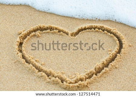 Heart drawn on the beach sand with sea foam