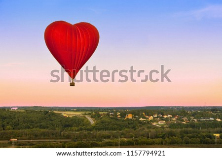 Heart flying red hot air balloon in sunset sky under green village in the forest.