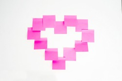 Heart formed by pink sticky notes, isolated in white background