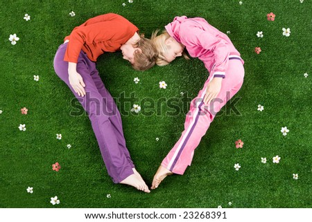 Heart formed by sleeping couple lying on green meadow - stock photo