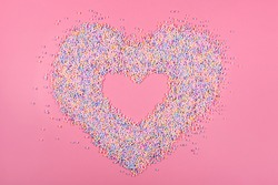 Heart frame made of pastel color balls on pink. Styrofoam or Polystyrene foam background. Mixed colorful sugar balls for sweets decoration. Rainbow sugar candies, dragee, confectionery. Love concept