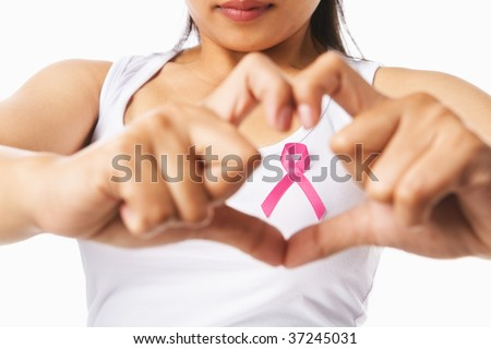 Heart framing from fingers on woman chest with pink badge to support breast cancer cause, PS: you can change the ribbon color to red to support AIDS cause as both using same symbol