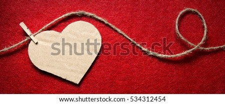 Heart from cardboard on rope with clothespin on red background with the gradient effect. Valentine\'s day, border design panoramic banner