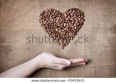 Heart from coffee beans and woman hand below on textured brown sack