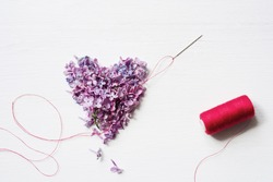 Heart from flowers of a lilac pierced with a needle and the coil of red threads on a white wooden board. Top view