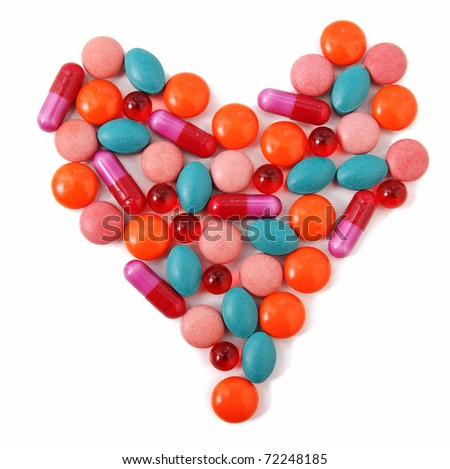 Heart from milticolor pills on white background