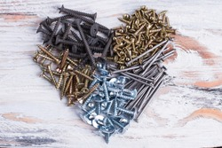 Heart from various screws and nails. Heap of metal screws in a shape of heart on wooden background.