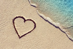 heart handwritten on a sand of beach with wave on background