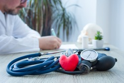 Heart health and diagnosis and treatment of cardiac disease concept photo. In foreground figure of red heart surrounded by stethoscope on table in background - blurry figure of doctor prescribing drug