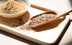Heart-healthy food - Close up of flaxseeds or linseeds in a wooden tea spoon with a pile of ground flaxseeds. Omega-3 fatty acid ALA, Lignans, Fiber, Antioxidant, Cardiovascular, Weight loss, diabetes