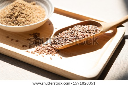 Photo of  Heart-healthy food - Close up of flaxseeds or linseeds in a wooden tea spoon with a pile of ground flaxseeds. Omega-3 fatty acid ALA, Lignans, Fiber, Antioxidant, Cardiovascular, Weight loss, diabetes