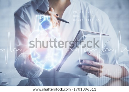Heart hologram over woman's hands writing background. Concept of Medical study. Multi exposure Foto stock ©