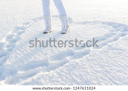 Heart in deep snow created by footsteps. Concept of love. Woman legs dressed in warm snow boots. Winter nature background. #1247611024