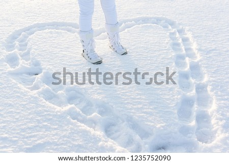 Heart in deep snow created with footsteps. Legs of woman with white snow boots on. #1235752090