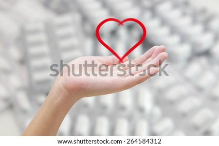 Heart in hands on pill blur background , healthy concept