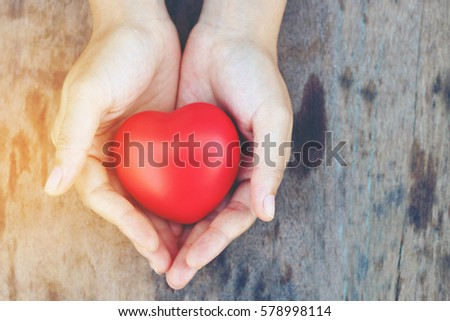 Heart in hands on wooden background in the morning light. Filtered color. vintage tone. #578998114