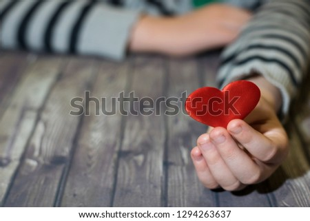 Heart in the hands of a child. Wooden background. Child holds a heart in his hands. Valentines Day. Give love, give life.