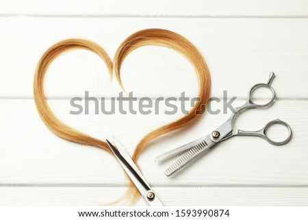 Heart made of cut hair curl and thinning  scissors. White wooden background.