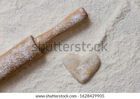 heart made of dough made by hand with on table sprinkled with white flour and rolling pin diagonally