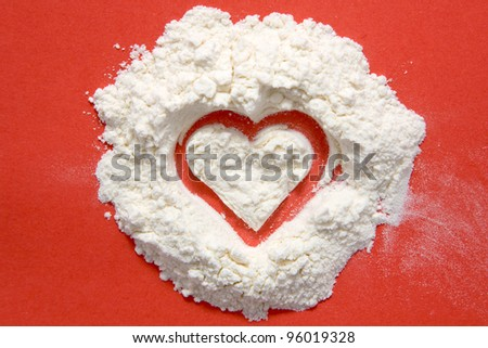 Heart made of flour. Isolated on red background