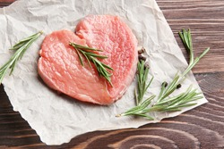 Heart made of fresh raw meat on wooden table