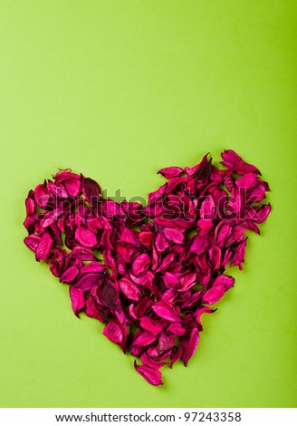 heart made ??of red rose petals on the paper
