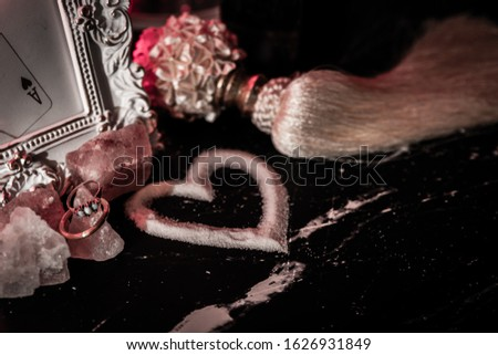Heart made of sugar on black marble table surrounded by old-fashioned items such as picture frame, tassel, crystals, rings.  Romance. Hearts