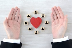 Heart object and wooden blocks with human pictogram surrounded by business man's hands