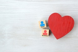 Heart object and wooden blocks with male and female human pictogram