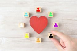Heart object surrounded by wooden blocks with colorful human pictogram